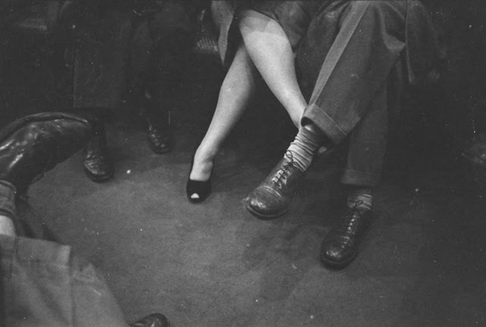 Couple playing footsies on a subway, 1946
